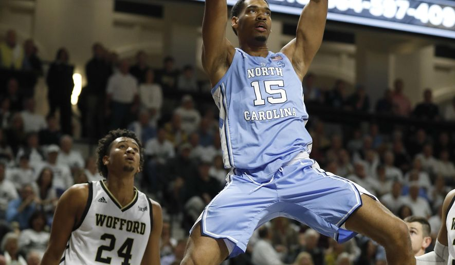 North Carolina's Garrison Brooks (15) dunks over Wofford's Keve Aluma (24) during the first half of an NCAA college basketball game in Spartanburg, S.C., Tuesday, Nov. 6, 2018. (AP Photo/Bob Leverone)
