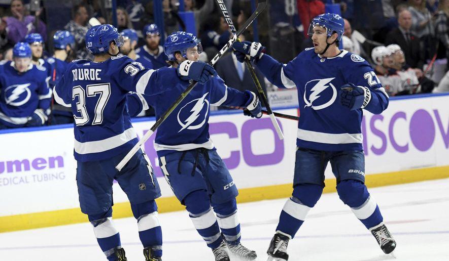 Tampa Bay Lightning center Yanni Gourde (37), center Brayden Point (21) and defenseman Ryan McDonagh (27) celebrate Gourde's second-period goal against the Edmonton Oilers during an NHL hockey game Tuesday, Nov. 6, 2018, in Tampa, Fla. (AP Photo/Jason Behnken)