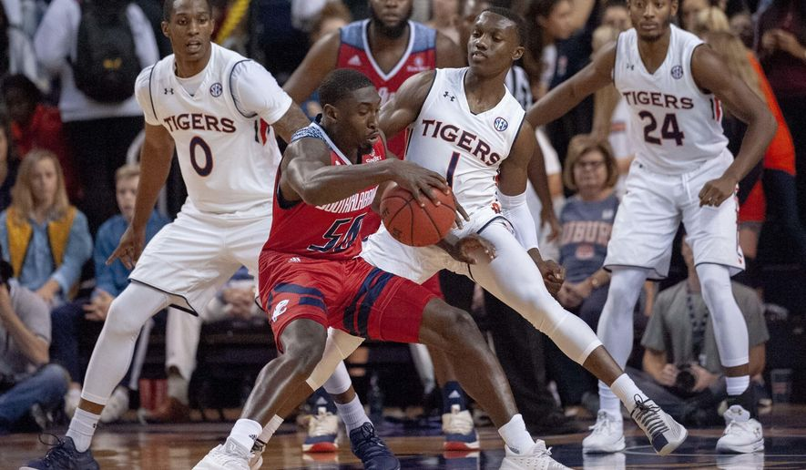 Auburn guard Jared Harper (1) defends against South Alabama guard John Pettway (50) during the first half of an NCAA college basketball game, Tuesday, Nov. 6, 2018, in Auburn, Ala. In background are Auburn forward Horace Spencer (0) and Auburn forward Anfernee McLemore (24). (AP Photo/Vasha Hunt)