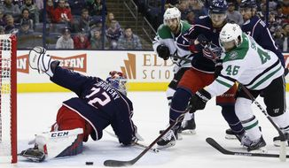 Columbus Blue Jackets' Sergei Bobrovsky, left, of Russia, makes a save as teammate Dean Kukan, right center, of Switzerland, Dallas Stars' Justin Dowling, left center, and Gemel Smith look for the rebound during the first period of an NHL hockey game Tuesday, Nov. 6, 2018, in Columbus, Ohio. (AP Photo/Jay LaPrete)