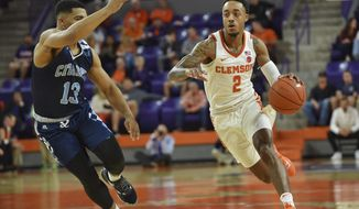 Clemson's Marcquise Reed dribbles to the basket while defended by The Citadel's Lew Stallworth during the first half of an NCAA college basketball game Tuesday, Nov. 6, 2018, in Clemson, S.C. (AP Photo/Richard Shiro)