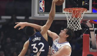 Minnesota Timberwolves center Karl-Anthony Towns, left, shoots as Los Angeles Clippers forward Montrezl Harrell defends during the first half of an NBA basketball game Monday, Nov. 5, 2018, in Los Angeles. (AP Photo/Mark J. Terrill)