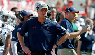 FILE - In this Sept. 29, 2018, file photo, Virginia head coach Bronco Mendenhall watches the action during the second half of an NCAA college football game in Raleigh, N.C. If first-place Pitt or second-place Virginia goes on to win the Coastal title this season, either would become the sixth different school in the last six seasons to win that side of the conference (AP Photo/Chris Seward, File) **FILE**