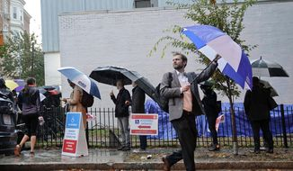 Voters line up in the rain outside Bright Family and Youth Center in the Columbia Heights neighborhood in Washington, Tuesday, Nov. 6, 2018. Across the country, voters headed to the polls Tuesday in one of the most high-profile midterm elections in years. (AP Photo/Pablo Martinez Monsivais) **FILE**