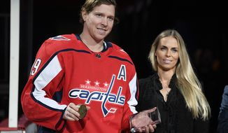 Washington Capitals center Nicklas Backstrom, left, of Sweden, and Liza Berg, Backstrom's fiance, pose during a ceremony where he was given a golden puck and a Tiffany crystal award prior to an NHL hockey game against the Pittsburgh Penguins, Wednesday, Nov. 7, 2018, in Washington. Backstrom was honored for recording 600 assists. (AP Photo/Nick Wass)