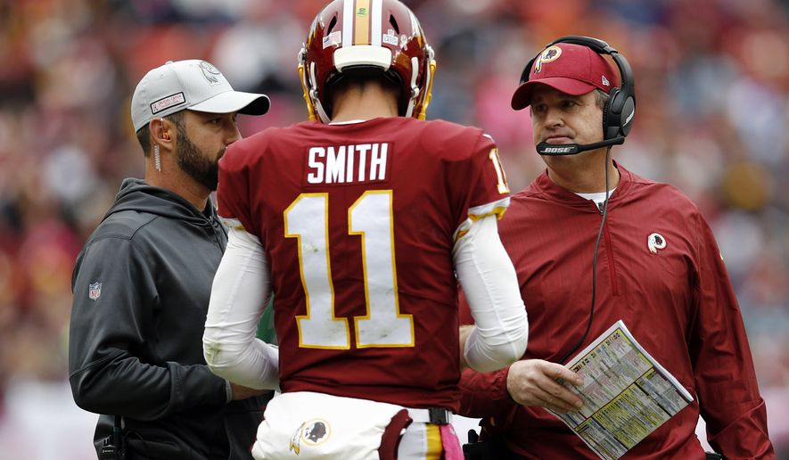 FILE - In this Oct. 14, 2018, file photo, Washington Redskins quarterback Alex Smith speaks with head coach Jay Gruden, right, during an NFL football game against the Carolina Panthers in Landover, Md. Gruden's Redskins have established a pattern: When they get a lead, they win; when they trail, they lose. The Redskins (5-3) are the only one of the NFL's 32 teams that both has managed to avoid a single loss after holding a lead and also has failed to come back to win a game after trailing. (AP Photo/Patrick Semansky, File)