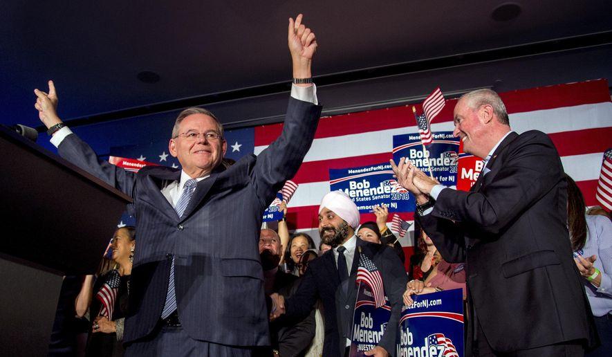U.S. Sen. Bob Menendez celebrates his re-election in Hoboken, N.J., Tuesday, Nov. 6, 2018, while Gov. Phil Murphy stands at right. (Tom Gralish/The Philadelphia Inquirer via AP)