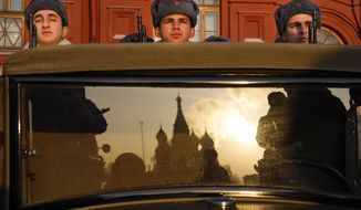 Russian soldiers dressed in Red Army World War II uniforms sit in the back of a truck as the St. Basil's Cathedral is reflected in the windshield prior to the start of the Nov. 7 parade in Red Square, with St. Basil Cathedral and thew Spasskaya Tower in the background, in Moscow, Russia, Wednesday, Nov. 7, 2018. The event marked the 77th anniversary of a World War II historic parade in Red Square and honored the participants in the Nov. 7, 1941 parade who headed directly to the front lines to defend Moscow from the Nazi forces. (AP Photo/Alexander Zemlianichenko)