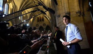 Prime Minister Justin Trudeau talks to reporters as he arrives to a caucus meeting on Parliament Hill in Ottawa, Ontario, on Wednesday, Nov. 7, 2018. (Sean Kilpatrick/The Canadian Press via AP)