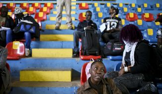 Haitian migrants wait to register for repatriation, at a local gym in Santiago, Chile, Wednesday, Nov. 7, 2018. After an unsuccessful migration experience to Chile, 176 Haitians were flown home on a military plane free of charge. (AP Photo/Esteban Felix)
