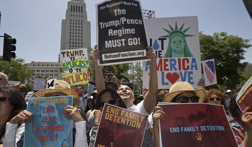"FILE - In this June 30, 2018 file photo, protesters gather to demonstrate against President Donald Trump's immigration policies in downtown Los Angeles. California voters elected a governor Tuesday who reflects their left-leaning, anti-Trump beliefs. The state's elected Democrats, and incoming Gov. Gavin Newsom, have relished their roles as leaders of the ""resistance"" to President Donald Trump, fighting Trump's efforts to roll back environmental protections and expanding protections for immigrants living in the state illegally. Their positions broadly reflect the views of most Californians, according to results from AP VoteCast, a survey of the American electorate. (AP Photo/Damian Dovarganes, File)"
