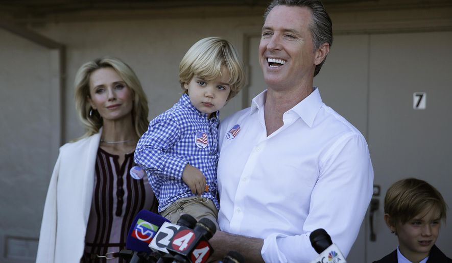 California gubernatorial Democratic candidate Gavin Newsom holds his son Dutch, 2, and talks with reporters after voting Tuesday, Nov. 6, 2018, in Larkspur, Calif. At left is his wife, Jennifer Siebel Newsom and at right his son Hunter, 7. (AP Photo/Eric Risberg)