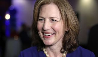 Congressional candidate Kim Schrier speaks with a reporter at an election night party for Democrats, Tuesday, Nov. 6, 2018, in Bellevue, Wash. (AP Photo/Elaine Thompson)