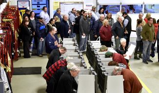 Voters wait on line to vote inside the fire bay at the Armada Twp. Fire Department, Tuesday , Nov.  6, 2018, in Armada Twp, Mich.  (Todd McInturf /Detroit News via AP)