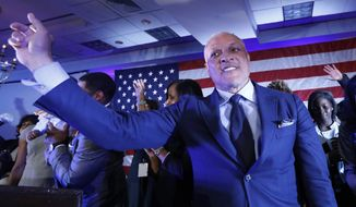 Mike Espy who is seeking to unseat appointed Sen. Cindy Hyde-Smith, R-Miss., and serve the last two years of the six-year term vacated when Republican Thad Cochran retired for health reasons, stands with family members and waves to a crowded ballroom of supporters following his speech in Jackson, Miss., Tuesday night, Nov. 6, 2018. Espy will face Hyde-Smith in a runoff on Nov. 27. (AP Photo/Rogelio V. Solis)