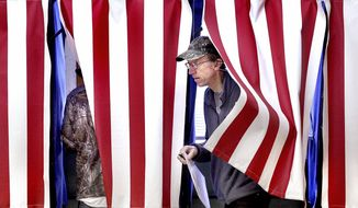A man steps out of a voting booth Tuesday, Nov. 6, 2018, at Town of Hamilton Town Hall in West Salem, Wis., in this file photo. (Peter Thomson/La Crosse Tribune via AP) **FILE**