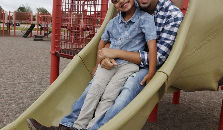 In an Oct. 11, 2018 photo, Rev. Aaron Zapata poses for a photo with his adopted son Kamdyn Zapata, 5, at UTPB Park's playground. Rev. Zapata and his wife Julie Zapata have two other adopted sons Kohen Zapata, 5, and 18-month-old Kyan Zapata. Rev. Zapata and his wife Julie Zapata have two other adopted sons Kohen Zapata, 5, and 18-month-old Kyan Zapata. (Jacob Ford/Odessa American via AP)
