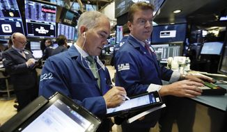 Trader Timothy Nick, center, works with specialist Michael O'Mara on the floor of the New York Stock Exchange, Wednesday, Nov. 7, 2018. Stocks are climbing in early trading on Wall Street as results of the U.S. midterm elections came in as investors had expected. (AP Photo/Richard Drew)