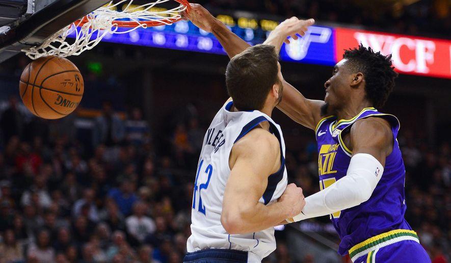 Utah Jazz guard Donovan Mitchell (45) dunks over Dallas Mavericks forward Maximilian Kleber (42) during the first half of an NBA basketball game Wednesday, Nov. 7, 2018, in Salt Lake City. (AP Photo/Alex Goodlett)