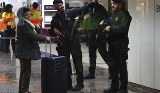Mossos d'Esquadra regional police in Catalonia cordon off one of the entrances at the city's main train station in Barcelona, Spain, Wednesday, Nov. 7, 2018. Authorities in Barcelona say the city's main train station has re-opened after it closed for more than one hour at Wednesday's rush hour while police searched for possible explosives in a suspicious suitcase. (AP Photo/Joan Monfort)