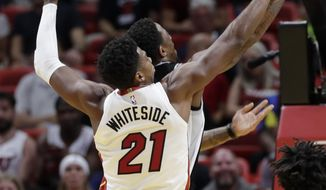Miami Heat center Hassan Whiteside (21) blocks a shot by San Antonio Spurs guard DeMar DeRozan during the first half of an NBA basketball game, Wednesday, Nov. 7, 2018, in Miami. (AP Photo/Lynne Sladky)