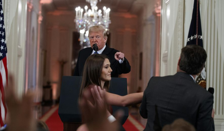 President Donald Trump watches as a White House aide reaches to take away a microphone from CNN journalist Jim Acosta during a news conference in the East Room of the White House, Wednesday, Nov. 7, 2018, in Washington. (AP Photo/Evan Vucci)