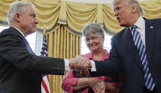FILE - In this  Feb. 9, 2017 file photo, President Donald Trump shakes hands with Attorney General Jeff Sessions, accompanied by his wife Mary, after he was sworn-in by Vice President Mike Pence, in the Oval Office of the White House in Washington. On Nov. 7, 2018, Sessions submitted his resignation in letter to Trump. (AP Photo/Pablo Martinez Monsivais, File)