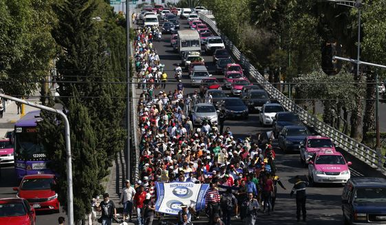 A group of Central American migrants, representing the thousands participating in a caravan trying to reach the U.S. border, undertake an hours-long march to the office of the United Nations' humans rights body in Mexico City, Thursday, Nov. 8, 2018. Members of the caravan which has stopped in Mexico City demanded buses Thursday to take them to the U.S. border, saying it is too cold and dangerous to continue walking and hitchhiking.(AP Photo/Rebecca Blackwell)