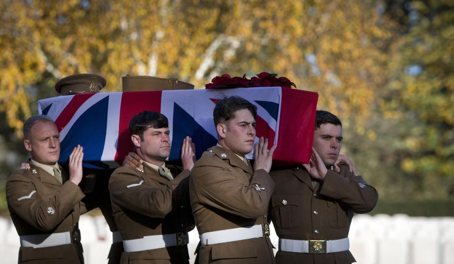 British soldiers carry the coffin of an unknown British World War I soldier during a reburial ceremony at Buttes New British cemetery in Zonnebeke, Belgium, Thursday, Nov. 8, 2018. The soldier was found near Zonnebeke in Aug. 2017. (AP Photo/Virginia Mayo)