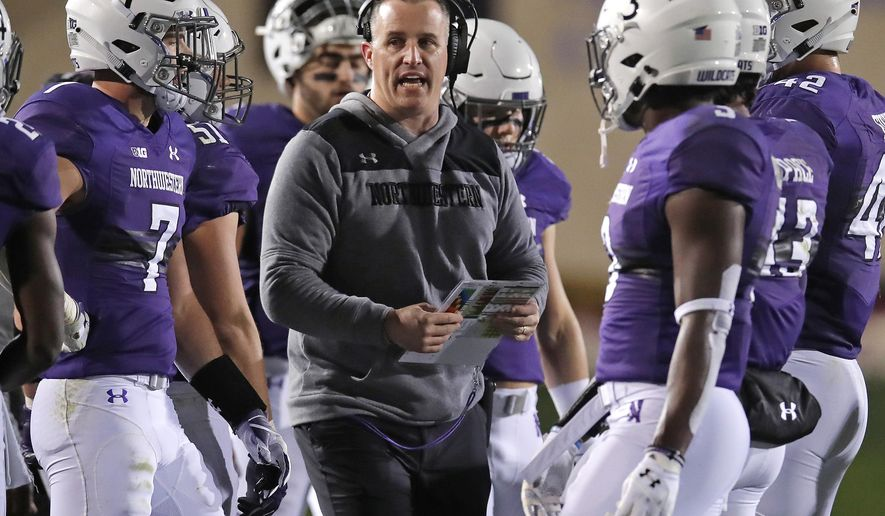 FILE - In this Saturday, Nov. 3, 2018, file photo, Northwestern coach Pat Fitzgerald talks with his players during the first half of an NCAA college football game against Notre Dame in Evanston, Ill. Northwestern can clinch the Big Ten West championship and its first appearance in the conference title game by winning two of its final three games.  (AP Photo/Jim Young)
