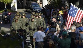 The body of Ventura County Sheriff's Department Sgt. Ron Helus is transported from the Los Robles Regional Medical Center Thursday, Nov. 8, 2018, in Thousand Oaks, Calif., after a gunman opened fire Wednesday inside a country music bar killing multiple people including Helus. (AP Photo/Mark J. Terrill)