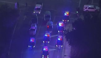 In this image made from aerial video, police vehicles block an intersection in the vicinity of a shooting in Thousand Oaks, California, early Thursday, Nov. 8, 2018.  Authorities say there were multiple injuries _ including one officer _ after a man opened fire in Southern California bar late Wednesday. (KABC via AP)