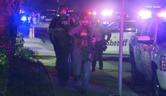 """In this image taken from video police officers and FBI agents run at the scene of a shooting, early Thursday morning, Nov. 8, 2018, in Thousand Oaks, Calif.  A hooded gunman dressed entirely in black opened fire on a crowd at a country dance bar holding a weekly """"college night"""" in Southern California, killing multiple people and sending hundreds fleeing including some who used barstools to break windows and escape, authorities said Thursday. The gunman was later found dead at the scene.  (RMG News via AP)"""