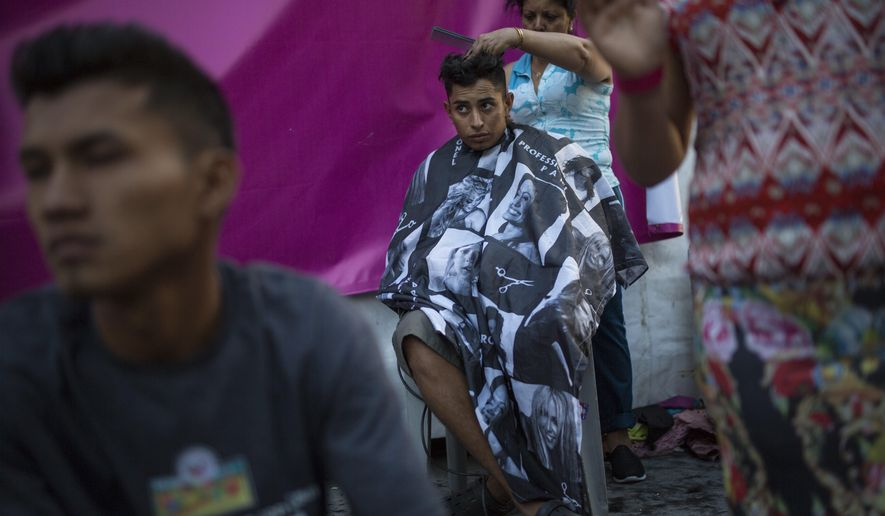 Honduran migrant Luis Fernando Barahona looks at an ongoing catholic mass while a hairdresser cuts his hair at a shelter at the Jesus Martinez stadium, in Mexico City, Wednesday, Nov. 7, 2018. Humanitarian aid converged around the stadium in Mexico City where thousands of Central American migrants winding their way toward the United States were resting Tuesday after an arduous trek that has taken them through three countries in three weeks. (AP Photo/Rodrigo Abd)