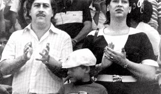 FILE - In this undated file photo, the late Pablo Escobar, former boss of the Medellin drug cartel, his wife Maria Henao and their son Juan Pablo, attend a soccer match in Bogota, Colombia. The widow of Pablo Escobar fell madly in love as a preteen with the man who would rise to be a ruthless drug lord, but says in a new book she felt raped when at age 14 he forced her to have an abortion, and over time came to view him as a cruel psychopath. (El Tiempo Photo via AP File)