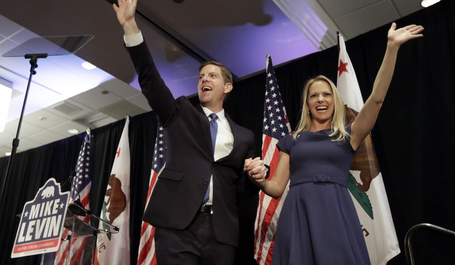Democratic congressional candidate Mike Levin, left, waves on stage alongside his wife Chrissy, right, as he speaks to supporters Wednesday, Nov. 7, 2018, in Del Mar, Calif. Levin faces Republican candidate Diane Harkey in the race for California's 49th congressional district. (AP Photo/Gregory Bull)
