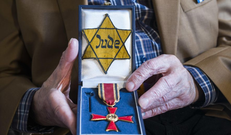 In this Nov. 5, 2018, photo Walter Frankenstein, born in 1924, witness of the Nov. 9, 1938 terror against Jews in Berlin and one of the few survivors of Auerbach'sches Waisenhaus orphanage shows a box with the Yellow badge the Nazis forced him to wear and with the Germany's Federal Cross of Merit he got 2014, during an interview with The Associated Press in Berlin. Frankenstein witnessed as the orphanage was attack by a Nazis during the terror night of Nov. 9, 1938. (AP Photo/Markus Schreiber)