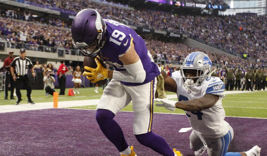 FILE - In this Nov. 4, 2018, file photo, Minnesota Vikings wide receiver Adam Thielen (19) catches a 2-yard touchdown pass ahead of Detroit Lions cornerback Nevin Lawson, right, during the first half of an NFL football game in Minneapolis. Thielen became the first player to have eight 100-yard receiving games to start a season, tying Calvin Johnson for the longest streak of such games. The former undrafted wide receiver has 78 catches for the Vikings. He's on pace to challenge Marvin Harrison's single-season record of 143. (AP Photo/Bruce Kluckhohn, File) **FILE**
