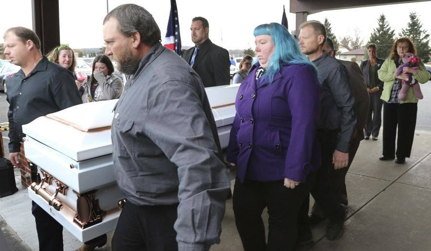 Judy Schneider of Chippewa Falls, the grandmother of Haylee Hickle and mother of Sara Schneider clutches a bear as the casket, holding them both is carried out of Chippewa Valley Bible Church after their funeral in Chippewa Falls, Wis., on Thursday, Nov. 8, 2018. The two were killed Saturday, Nov. 3 in a hit-and-run  accident. (Dan Reiland/The Eau Claire Leader-Telegram via AP)