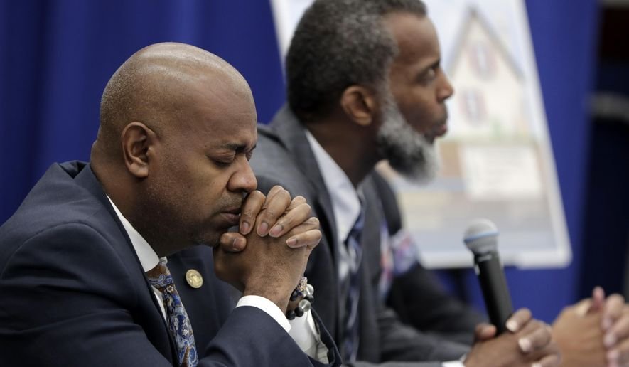 Newark Mayor Ras Baraka, left, listens to a reporters question while sitting with Kareem Adeem, the city's deputy director of water and sewer utilities, right, during a news conference talking about levels of lead in the city's tap water, Thursday, Nov. 8, 2018, in Newark, N.J. Baraka said Thursday his administration is taking multiple steps to address the high levels caused by aging lead water lines. Meanwhile, a lawsuit claims the city hasn't taken adequate precautions and has misled residents. Between 15,000 and 18,000 homes are estimated to have the lead lines. (AP Photo/Julio Cortez)