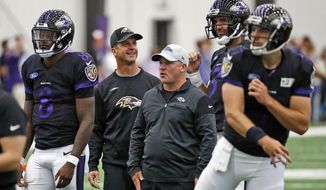 FILE - In this July 24, 2018, file photo, Baltimore Ravens head coach John Harbaugh, second from left, talks with quarterback Joe Flacco, second from right, during an NFL football practice in Owings Mills, Md. Also pictured, from left, are quarterback Lamar Jackson, quarterbacks coach James Urban and quarterback Josh Woodrum. The emergence of first-round draft pick Lamar Jackson and a three-game losing streak have raised questions about the relationship of Harbaugh and Flacco, who reached the postseason in their first five years together and capped the run with a Super Bowl victory. (AP Photo/Patrick Semansky, File)