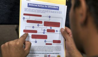 FILE - In this Aug. 15, 2012 file photo, a legal immigrant reads a guide of the conditions needed to apply for Obama-era Deferred Action for Childhood Arrivals (DACA) program at the Coalition for Humane Immigrant Rights, CHIRLA offices in Los Angeles. A U.S. appeals court ruled Thursday, Nov. 8, 2018, that President Donald Trump cannot immediately end the Obama-era program shielding young immigrants from deportation. A three-judge panel of the 9th U.S. Circuit Court of Appeals unanimously kept in place a preliminary injunction blocking Trump's decision to phase out the DACA program. (AP Photo/Damian Dovarganes, File)