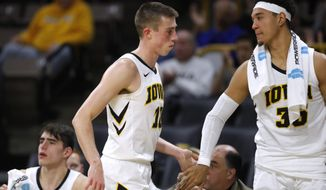 Iowa guard Joe Wieskamp is greeted by teammate Cordell Pemsl, right, at the end of an NCAA college basketball game against UKMC, Thursday, Nov. 8, 2018, in Iowa City, Iowa. (AP Photo/Charlie Neibergall)
