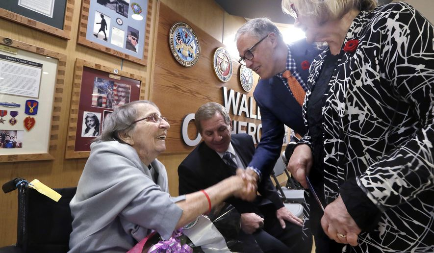 """U.S. Army Nurse Corps veteran Frances E. Harman, 98, left, who served as a first lieutenant in World War II, smiles as she is greeted by Gov. Jay Inslee and his wife Trudi Inslee before a ceremony honoring her service Thursday, Nov. 8, 2018, in Seattle. Harman's son, David Harman, is seated beside her. Harman is the first female veteran to be honored at the annual VA Puget Sound Veterans Day event, where a plaque honoring her will join a """"Wall of Heroes"""" at the health care facility. She served in the burn unit of a field hospital in New Guinea. (AP Photo/Elaine Thompson)"""