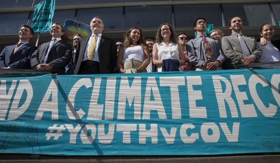 In this July 18, 2018, photo, lawyers and youth plaintiffs lineup behind a banner after a hearing before Federal District Court Judge Ann Aiken between lawyers for the Trump Administration and the so-called Climate Kids in Federal Court in Eugene, Ore. The lawsuit against the U.S. government for being slow to address climate change is on hold again, after a federal appeals court Thursday, Nov. 8, 2018, granted the Trump administration's motion for a temporary stay. The constitutional climate lawsuit was brought by 21 young Americans and is supported by Our Children's Trust. (Chris Pietsch/The Register-Guard via AP) **FILE**