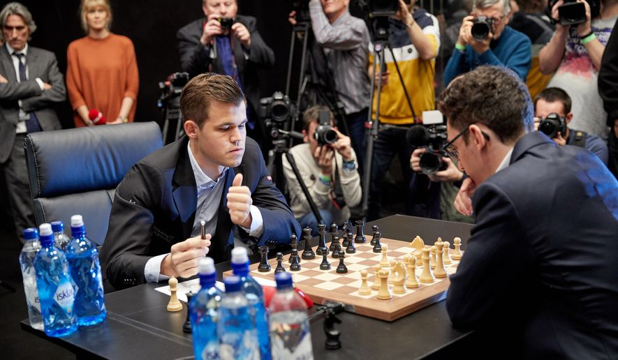 69d491c57507 World chess champion Magnus Carlsen of Norway (left) ponders a move early  in the