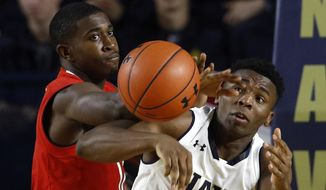 Maryland guard Darryl Morsell, left, and Navy guard Hasan Abdullah chase after a rebound in the first half of an NCAA college basketball game at the Veterans Classic tournament in Annapolis, Md., Friday, Nov. 9, 2018. (AP Photo/Patrick Semansky)