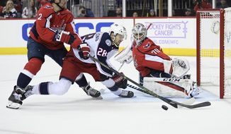 Columbus Blue Jackets right wing Oliver Bjorkstrand (28), of Denmark, battles for the puck against Washington Capitals defenseman Matt Niskanen (2) and goaltender Braden Holtby (70) during the first period of an NHL hockey game, Friday, Nov. 9, 2018, in Washington. (AP Photo/Nick Wass)
