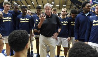 Former Connecticut men's basketball head coach Jim Calhoun talks to his team before the tip off in his debut as the head coach of the University of St. Joseph in an NCAA college basketball game against the William Paterson University, Friday, Nov. 9, 2018 at the Ray Oosting Gymnasium at Trinity College in Hartford, Conn. (Cloe Poisson/Hartford Courant via AP)