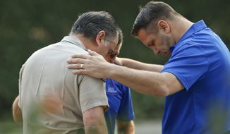 Ventura County Sheriff's Office Capt. Garo Kuredjian, left, embraces chaplains with the Billy Graham Rapid Response Team (RRT) as they pray near the site of Wednesday's mass shooting in Thousand Oaks, Calif., Friday Nov. 9, 2018. Investigators continue to work to figure out why an ex-Marine opened fire Wednesday evening inside a Southern California country music bar, killing multiple people.  (AP Photo/Damian Dovarganes)